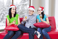 Three teenagers drinking champagne group of young people in santa hat Royalty Free Stock Image