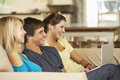 Three Teenagers  Sitting On Sofa At Home Using Tablet Computer And Laptop Whilst Watching TV Royalty Free Stock Photo