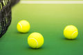Three tennis balls on green hard court Royalty Free Stock Photo