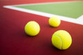 Three tennis balls on hard court Royalty Free Stock Photo
