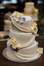 Three tier champagne colored wedding cake with yellow and purple flowers a in cream white Stock Images