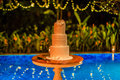 Three tier layered wedding cake with white marzipan icing decorated with orchids on a table near the pool. Royalty Free Stock Photo