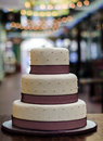 Three tier wedding cake white burgundy a in with pearls and a band around the Royalty Free Stock Images