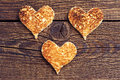 Three toast bread in the shape of hearts on wooden background Stock Photography