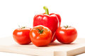 Three tomatoes and a red pepper on a wooden board. Royalty Free Stock Photo