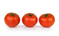 Three tomatoes in water droplets on white isolated background Royalty Free Stock Images