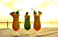 Three tropical drinks pier overlooking caribbean sea sunset Royalty Free Stock Images