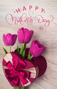 Three tulip in red gift box in form of heart and text Happy mothers day. Calligraphy lettering hand draw Royalty Free Stock Photo