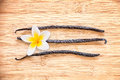 Three vanilla pods with a flower aligned on wood wooden background Stock Photo