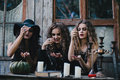 Three vintage witches perform magic ritual throwing sweet at a table on the eve of halloween Royalty Free Stock Photo