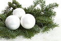 Three white christmas balls and pine tree over white background Royalty Free Stock Photo