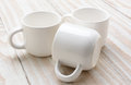 Three white mugs closeup on a rustic whitewashed wood table still life study of on horizontal format Royalty Free Stock Images