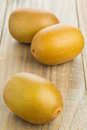 Three whole golden kiwifruit kiwi actinidia chinensis on wooden background Royalty Free Stock Photo