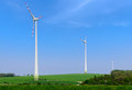 Three wind generators power on the green meadow Stock Photography