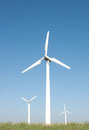 Three wind turbines clean blue sky background Stock Photos