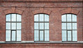 Three window on a red bric wall fabric Stock Photography