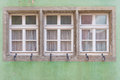 Three windows on classic green old wall in Europe Royalty Free Stock Photo