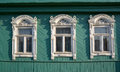 Three windows with white carved platbands Royalty Free Stock Photo