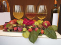 Three wine glasses bottles rose apples and nuts composition on table Royalty Free Stock Image