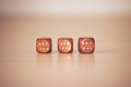 Three woden dices on light beige table wooden Stock Image