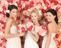 Three women with background full of roses Royalty Free Stock Photo