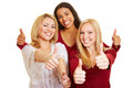 Three women holding thumbs up happy young their Royalty Free Stock Photo