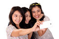 Three women selfie with front camera isolated cheerful asian taking self shot picture using of a smartphone on white background Royalty Free Stock Photography