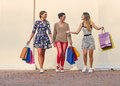 Three women with shopping bags freetime walking around group walking on city street against wall Royalty Free Stock Photos