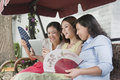Three women smiling and relaxing with fans and tablet outdoors Stock Photos