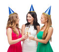 Three women wearing hats with champagne glasses celebration drinks friends bachelorette party birthday concept smiling blue Stock Photo