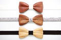 Three wooden bow ties with white, grey and black ribbons. Flat lay, isolated. Team work, career, wedding, eco concept. Royalty Free Stock Photo
