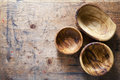 Three wooden bowls from olive tree on a wooden background Stock Photos