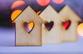 Three wooden houses with hole in form of heart on colorful bokeh red and orange background Stock Photos