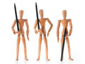 Three wooden mannequins holding pens as armed guards