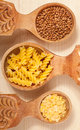 Three wooden spoon with buckwheat, lentil and pasta fusilini Royalty Free Stock Photo