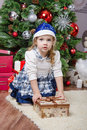 Three year old girl with a gift in Christmas tree Royalty Free Stock Photo
