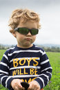 Three year old sulky boy in a farm field Royalty Free Stock Photo