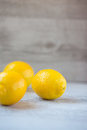 Three yellow lemons on table with copy space Royalty Free Stock Photo
