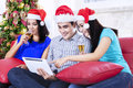 Three young asian friends drink champagne at home wearing santa hat Stock Photo