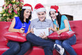 Three young asian friends drinking wine wearing santa hat at home Stock Photos