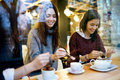 Three young beautiful women drinking coffee at cafe shop. Royalty Free Stock Photo