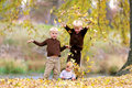 Three Young Children playing in Fallen Leaves Royalty Free Stock Photo