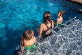 Three young children sitting pool water together talking swimming end summers day having fun Royalty Free Stock Image