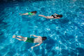 Three young children swimming underwater pool water together end summers day having fun Stock Photos