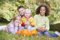 Three young friends with baby and pumpkins Royalty Free Stock Image