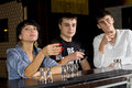 Three young friends downing shots of vodka enjoying an evening out together as they sit at a counter in a pub or nightclub Stock Images