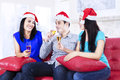 Three young friends drinking champagne in santa hat Stock Photography