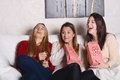 Three young friends eating popcorn and watching movies. Royalty Free Stock Photo