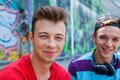 Three young friends happy portrait of teens boy with his by painted wall looking at camera Stock Images