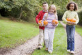 Three young friends walking on path with pumpkins Royalty Free Stock Photo